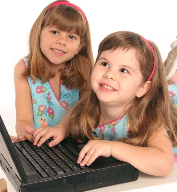 2 meisjes werken of spelen aan een pc laptop computer liggend beeld