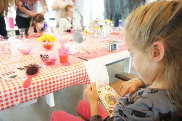 Een roze tafel met lekkers en een speelboekje voor de dochters, en de mama's konden aan de slag