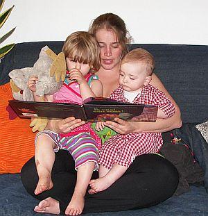 moeder leest voor het slapen gaan nog een boekje voor aan haar 2 kinderen